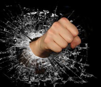 Photo of fist through glass