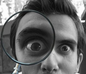 Photo of man looking through magnifying glass