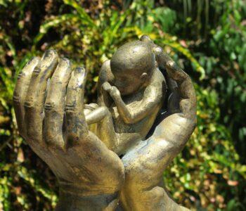 Photo of statue - infant held in between two hands